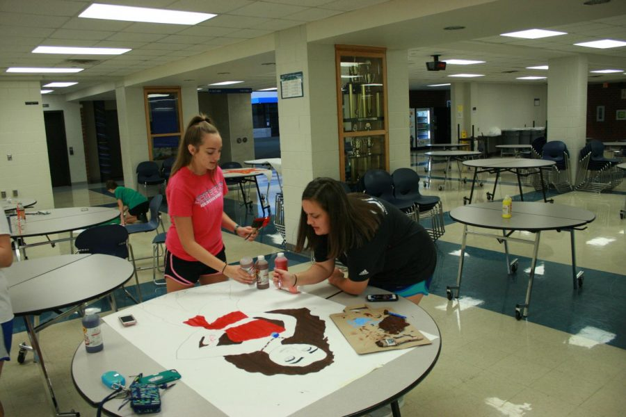 sophomores+Emma+Gibbs+and+Alexa+Preister+work+to+create+Disney+character+decorations.+Student+Council+members+work+past+midnight+to+decorate+the+night+before+the+dance.