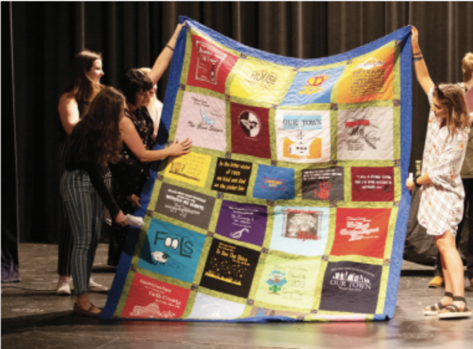 A COMMEMORATIVE QUILT: Students present a quilt of play and musical T-shirts from the last 10 years. The quilt was commissioned by English teacher drama assistant Kari Murphy.
