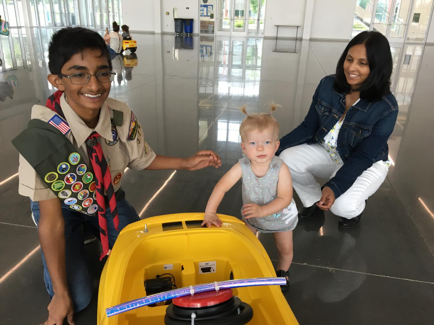 Fichadia poses with a toddler who has just reached her redesigned race car