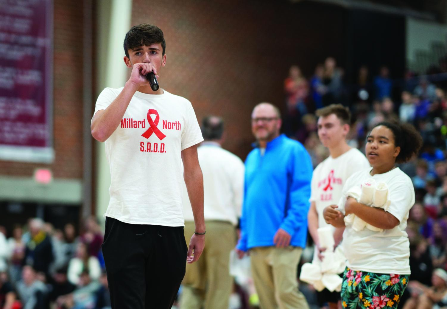 Senior Luke Uhlig raises awareness for drunk driving during pep rally. Senior Mia Obure hands out T-shirts to the crowd.