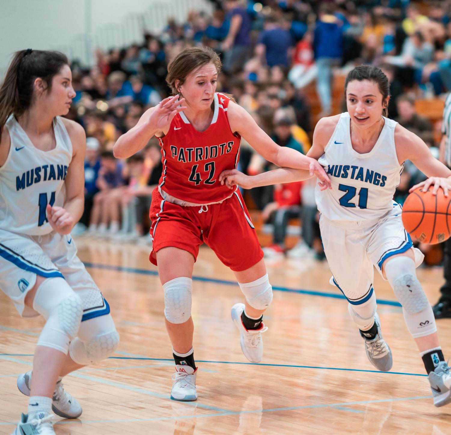 Senior Nicole Avila-Ambrosi takes the ball down the court while defending against a Millard South Patriot. the Mustangs took on their rivals, the Patriots, at the Stable on Jan. 31st.