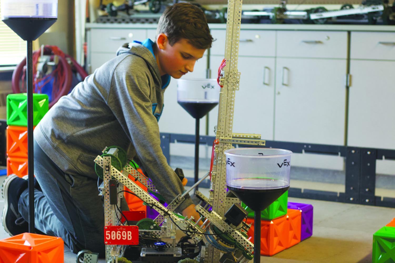 Freshman Patrick Stolinski makes adjustments to his team's robot. Stolinski plans to take a Robotics class next year.