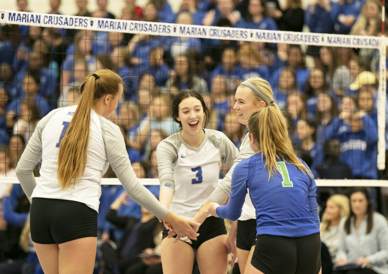 (left to right) Senior Mckenna Ruch, junior Mollie Fee, senior Lauren Maciejewski, and sophomore Kate Galvin high five after they score on Marian. Millard North won the game 3-2.